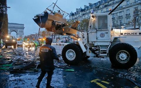 A bulldozer levels the barricade in the aftermath of a protest against the rising of the fuel taxes at the Champs Elysees avenue in Paris - Credit: Michel Euler/AP