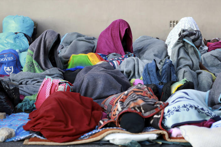 Refugees sleep on a sidewalk in Cape Town, South Africa, Friday, March 27, 2020, after South Africa went into a nationwide lockdown for 21 days in an effort to mitigate the spread to the coronavirus. The new coronavirus causes mild or moderate symptoms for most people, but for some, especially older adults and people with existing health problems, it can cause more severe illness or death. (AP Photo/Nardus Engelbrecht)