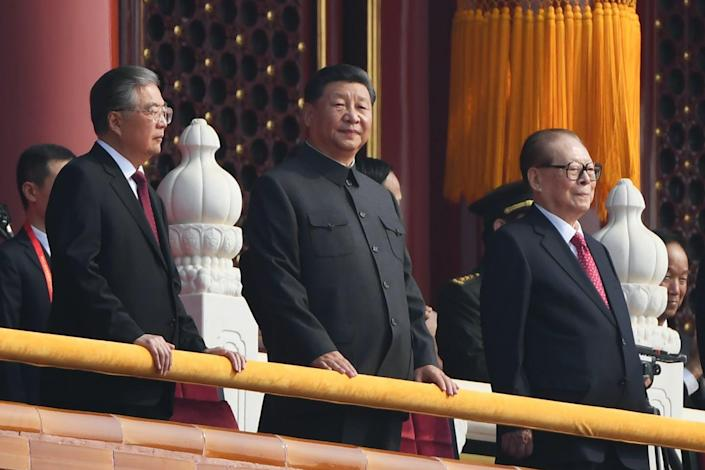 Xi stands on a balcony in black suit with a Mao-style collar, flanked by his predecessors