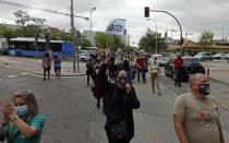 """People attend a protest against the handling of the coronavirus pandemic in Madrid, Spain, Sunday, Sept. 20, 2020. Spaniards are protesting in Madrid against the handling of the coronavirus pandemic by the regional head of the Spanish capital, who has placed new restrictions on neighborhoods with the highest contagion rates. The Spanish capital's rate of transmission is more than double the national average, which already leads European contagion charts. The sign reads in Spanish """"enough!"""" (David Obach/Europa Press via AP)"""