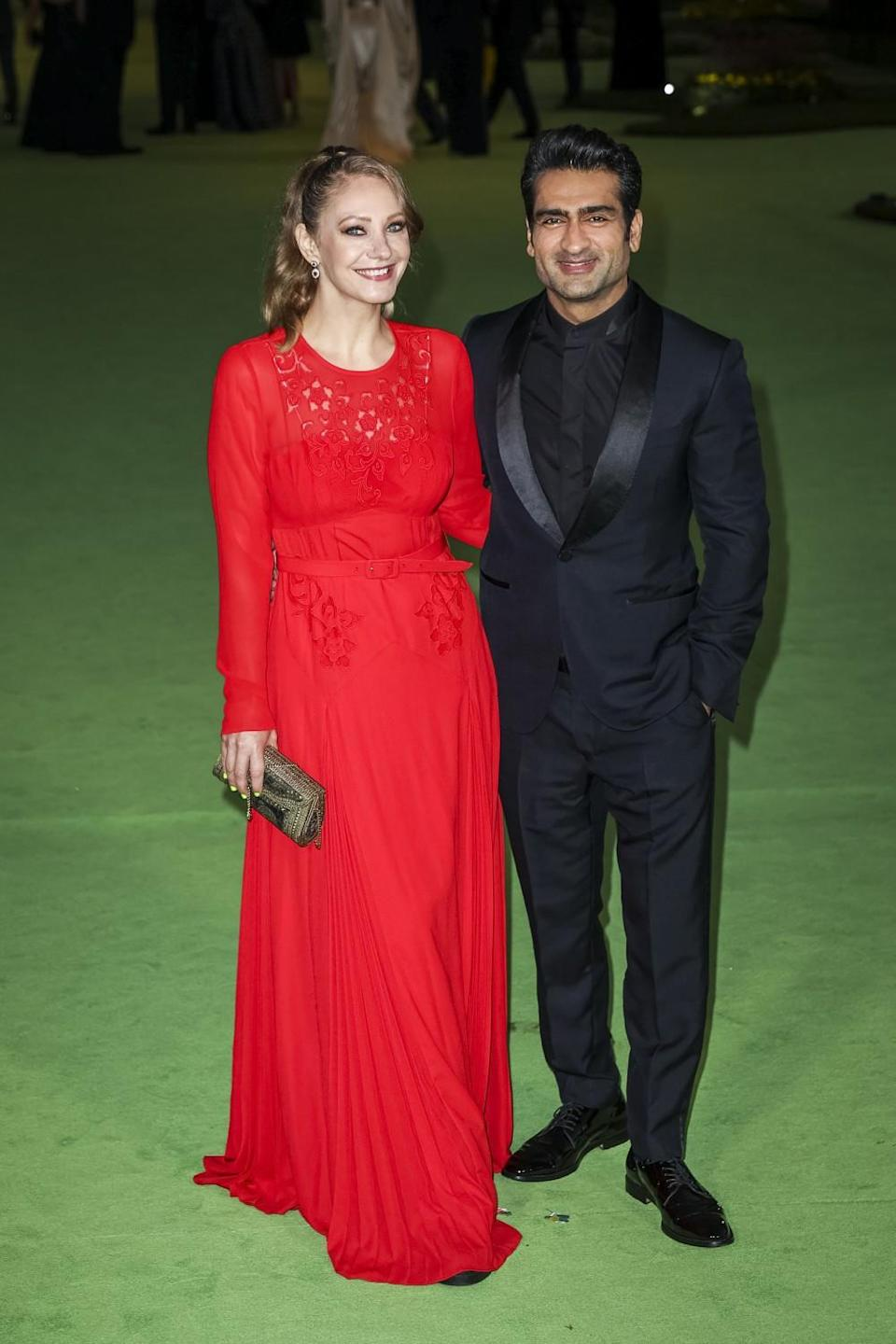 A woman in a red dress and a man in a black suit posing on a green carpet