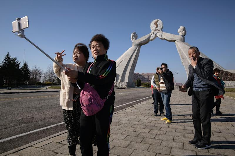 Tourists from China pose for photos before the Three Charters monument in the North Korean capital Pyongyang (AFP Photo/Ed JONES)
