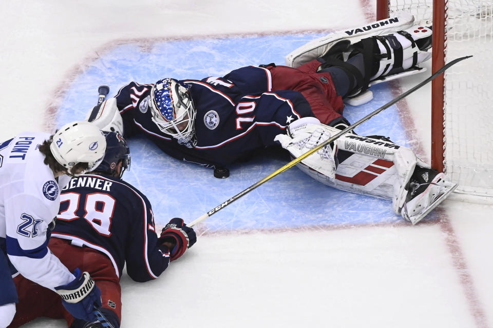 Columbus Blue Jackets goaltender Joonas Korpisalo (70) covers the puck as Tampa Bay Lightning center Brayden Point (21) and Blue Jackets center Boone Jenner (38) look for a rebound during the third period of Game 3 of an NHL hockey first-round playoff series, Saturday, Aug. 15, 2020, in Toronto. (Nathan Denette/The Canadian Press via AP)