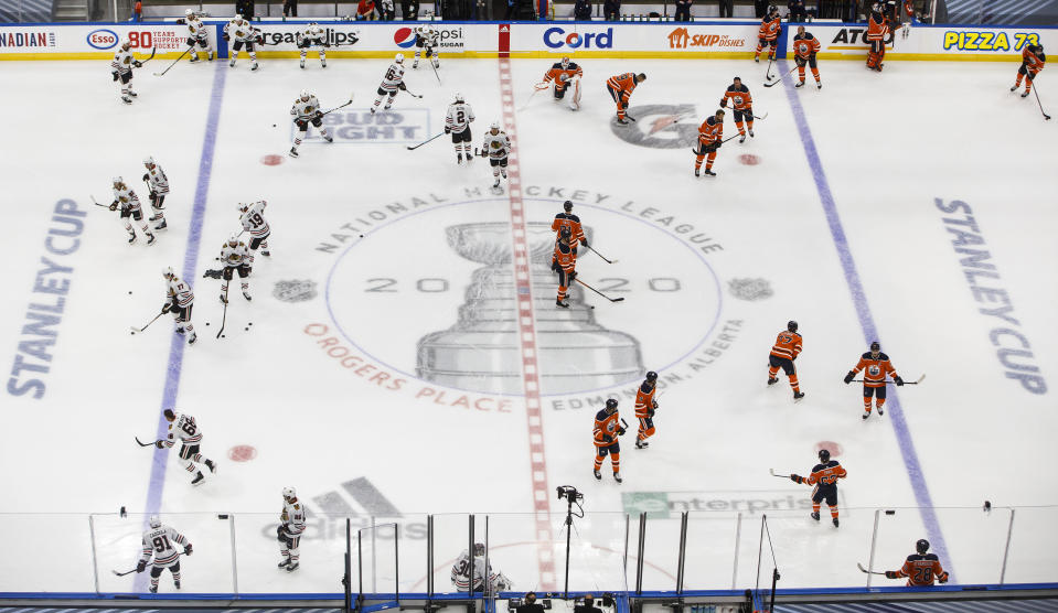The Edmonton Oilers,right, and Chicago Blackhawks warm up before an NHL hockey Stanley Cup playoff game, in Edmonton, Alberta, Saturday, Aug. 1, 2020. (Jason Franson/The Canadian Press via AP)