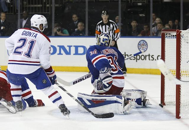 Montreal Canadiens right wing Brian Gionta (21) and New York Rangers goalie Henrik Lundqvist (30), of Sweden, look back as the puck skirts the goal line during the third period of Game 4 of the NHL hockey Stanley Cup playoffs Eastern Conference finals, Sunday, May 25, 2014, in New York. (AP Photo/Kathy Willens)