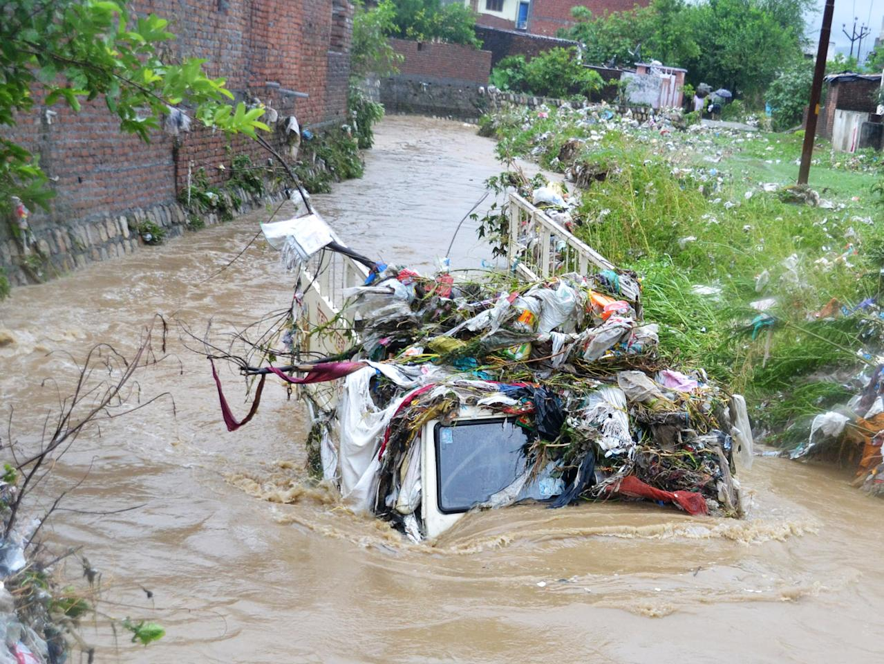 Trash covers a truck submerged in flood waters from heavy monsoon rains in Dehradun in the Indian state of Uttrakhand on June 17, 2013. Heavy rains lashed parts of north India Monday, resulting in the deaths of at least 18 people, as the annual monsoon covered the country nearly two weeks ahead of schedule, officials said. More than a dozen people lost their lives due to record downpours in Uttarakhand state, situated in the foothills of the Himalayas, a local official said. AFP PHOTO/ STR        (Photo credit should read STRDEL/AFP/Getty Images)