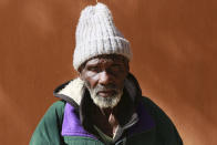 """Rodrick Bhatare an elderly man in his 90s sits outside Melfort Old People's home on the outskirts of Harare, Zimbabwe, Sunday, July 25, 2021. Just a week after arriving at the facility, Rodrick Bhatare, in his 90s, said he felt a bittersweet moment at the celebration for a 103-year old fellow resident. """"I haven't been this happy in a very long time,"""" he said. """"I just wished I was doing it with my family."""" Hard-hit by the pandemic, his family could no longer provide for him, he said. The economic ravages of COVID-19 are forcing some families in Zimbabwe to abandon the age-old tradition of taking care of their elderly. (AP Photo/Tsvangirayi Mukwazhi)"""