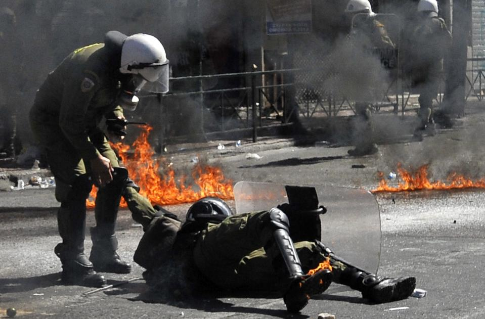 A riot policeman assists a colleague after he was hit by a petrol bomb thrown by protester during clashes in Athens Wednesday Sept. 26, 2012. Greek workers walked off the job Wednesday for the first general strike since the country's coalition government was formed in June, as the prime minister and finance minister hammered out a package of euros 11.5 billion ($14.87 billion) in spending cuts. Athens has struggled to come up with more punishing austerity measures that would be acceptable to its rescue creditors, with disagreements arising between the three parties that make up the coalition government. Greece's creditors have demanded more fiscal reforms if they are to continue handing out rescue loans preventing the country from a messy default that could roil the euro. (AP Photo/Nikolas Giakoumidis)