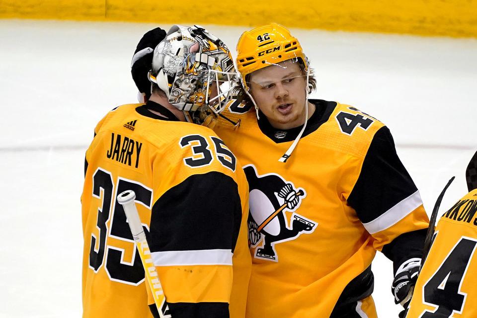 Pittsburgh Penguins' Kasperi Kapanen (42) celebrates with goaltender Tristan Jarry after the team's 5-1 win over the New Jersey Devils in an NHL hockey game in Pittsburgh, April 22, 2021. (AP Photo/Gene J. Puskar)
