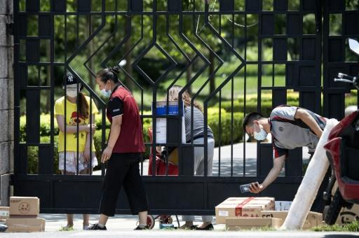 Residents wait behind a gate for items they ordered online at a compound under lockdown