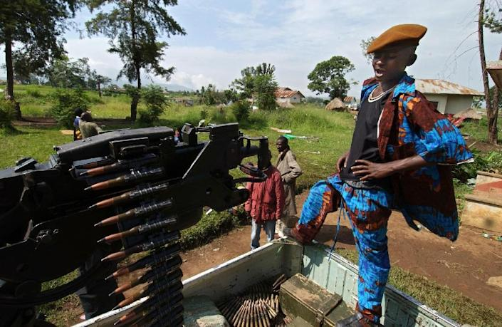 A child fighter stands by a machine gun fixed on a pickup at a military camp in Bunia, in northeastern DR Congo, in 2003 (AFP Photo/Eric Feferberg)