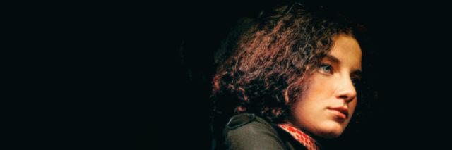 Woman with tan skin and curly hair looking thoughtfully into the distance.
