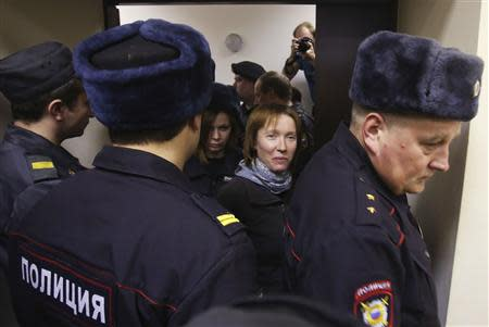 "Yekaterina Zaspa (C), the""Arctic Sunrise"" ship's doctor, and one of the 30 people arrested over a Greenpeace protest at the Prirazlomnaya oil rig, is escorted before a court session in St. Petersburg, November 18, 2013. REUTERS/Maxim Zmeyev"