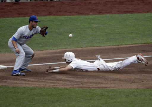 Texas' Duke Ellis, right, beats the throw to Florida third baseman Jonathan India (6) in the first inning of an NCAA College World Series baseball elimination game in Omaha, Neb., Tuesday, June 19, 2018. (AP Photo/Nati Harnik)