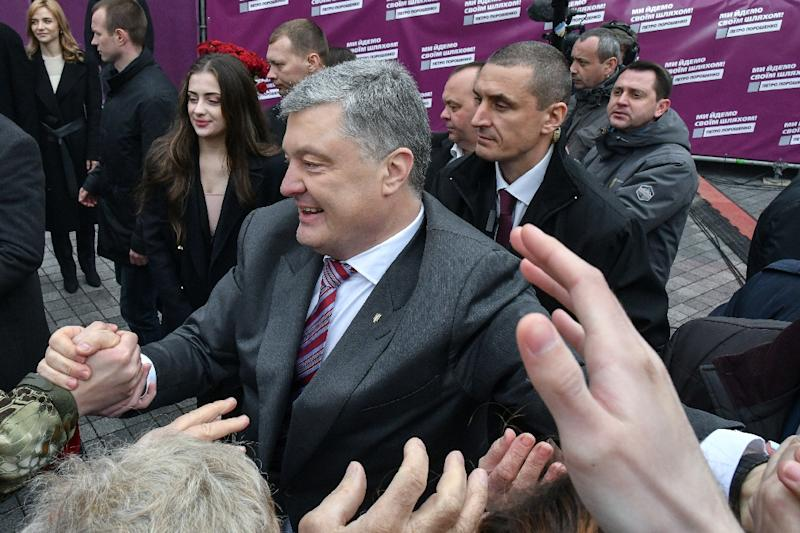 Poroshenko's backers praise him for rebuilding the army,securing an Orthodox Church independent of Russia and winning visa-free travel to Europe.But critics fault him on his efforts to fight graft,improve living standards or uphold the rule of law (AFP Photo/Genya SAVILOV)