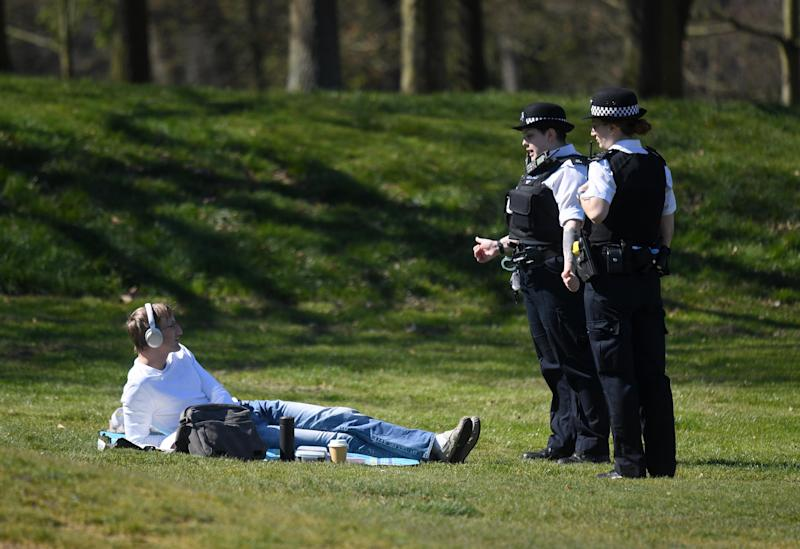 Police enforcing lockdown restrictions speak to a sunbather in a London park (EPA)