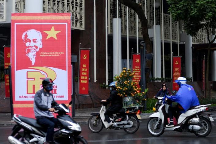 Motorbikes ride on a decorated avenue welcoming the 13th National Congress of the Communist Party of Vietnam in Hanoi