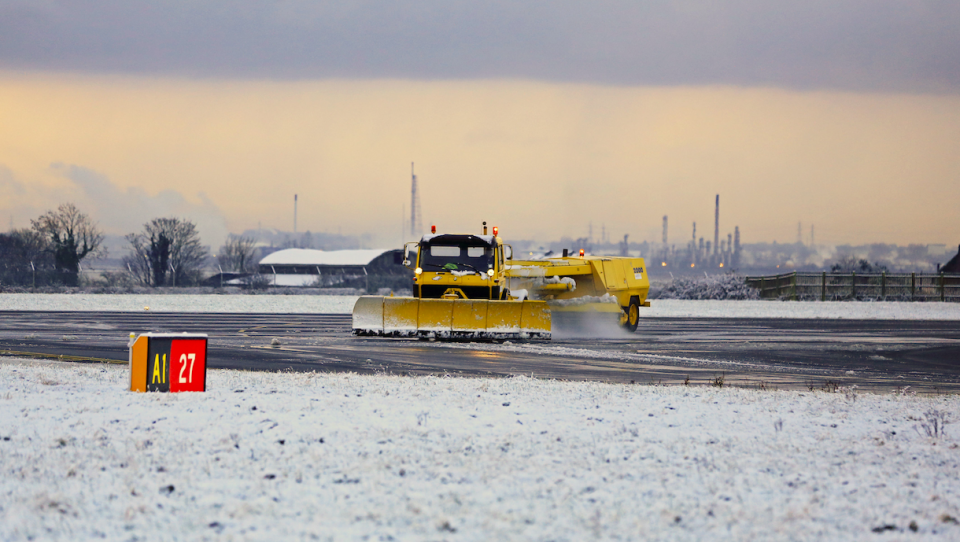 <em>Snow ploughs at Liverpool John Lennon Airport (PA)</em>