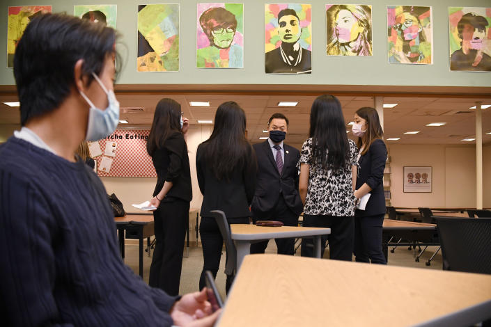 In this Monday, May 10, 2021 photo, teacher Clarissa Tan, right, and Asian American Student Union students talk with Connecticut Attorney General William Tong, center, during a program for Asian Pacific American Heritage Month at Farmington High School in Farmington, Conn. The year of anti-Asian violence has led students and teachers to advocate for reexamining how Asian American studies and history are taught in public schools. (AP Photo/Jessica Hill)