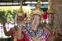 Thai classical dancers wearing face shield to help curb the spread of the coronavirus perform at the Erawan Shrine in Bangkok, Thailand, Thursday, May 28, 2020. Thai government continues to ease restrictions related to running business in capital Bangkok that were imposed weeks ago to combat the spread of COVID-19.(AP Photo/Sakchai Lalit)