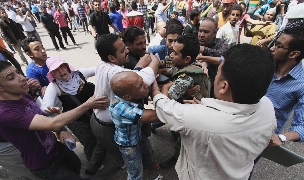 Protesters clash with a Egyptian military solider outside the Defense Ministry in Cairo, Egypt, Wednesday, May 2, 2012. Suspected supporters of Egypt's military rulers attacked predominantly Islamist anti-government protesters outside the Defense Ministry in Cairo Wednesday, setting off clashes that left more than ten people dead as political tensions rise three weeks before crucial presidential elections. (AP Photo)