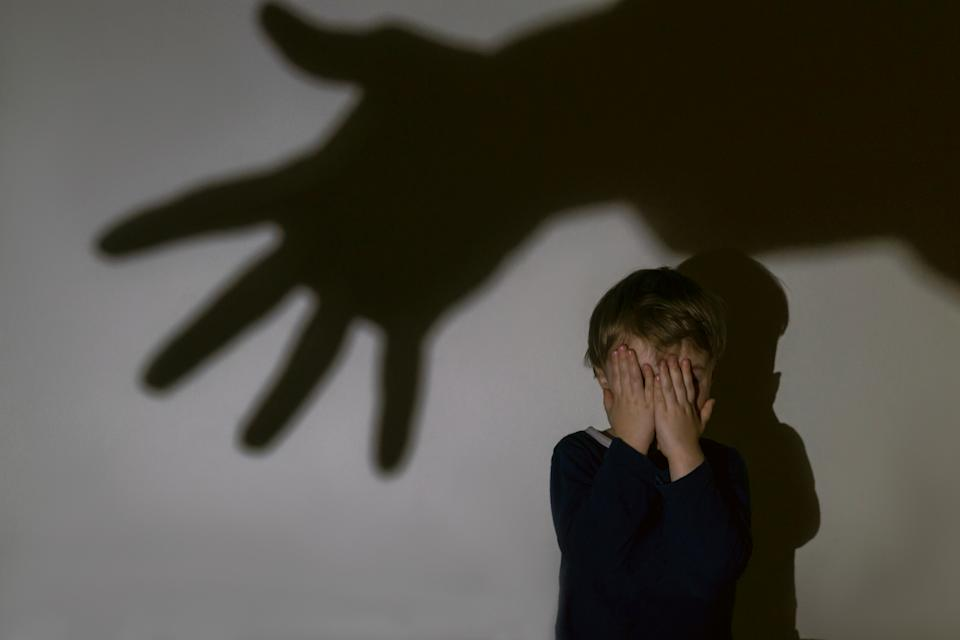 A little boy and scary shadow of hand on a light background for a fear or kidnapping concept. Boy closed eyes with hands.