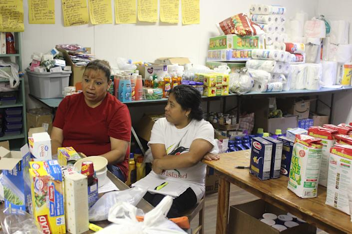 Yolanda Soto, left, and Dorcas Diego help coordinate donations for families affected by immigration raids Aug. 7.
