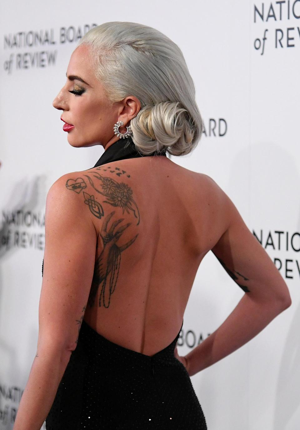 """<p>Lady Gaga's back is adorned in tattoos with a daisy chain and monster claw (in tribute to her fans) sitting pretty. Interestingly, the singer only has ink on the left side of her body after her father <a rel=""""nofollow noopener"""" href=""""https://www.eonline.com/uk/news/585294/lady-gaga-gets-huge-monster-paw-tattoo-on-her-back-flashes-naked-butt-in-the-process-see-pics"""" target=""""_blank"""" data-ylk=""""slk:asked"""" class=""""link rapid-noclick-resp"""">asked</a> her to """"keep one side slightly normal"""". <em>[Photo: Getty]</em> </p>"""