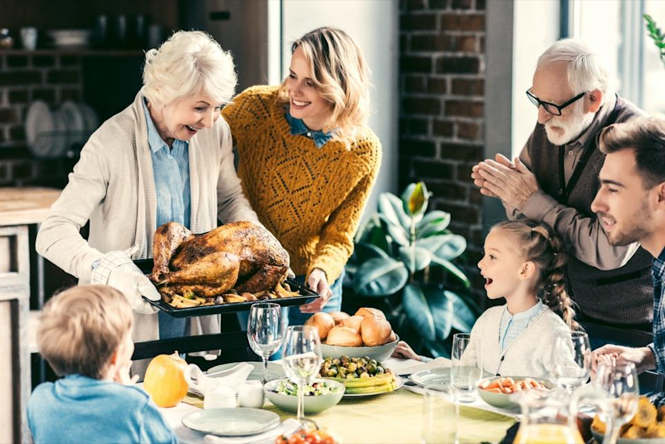 grandmother carrying turkey for family on thanksgiving dinner