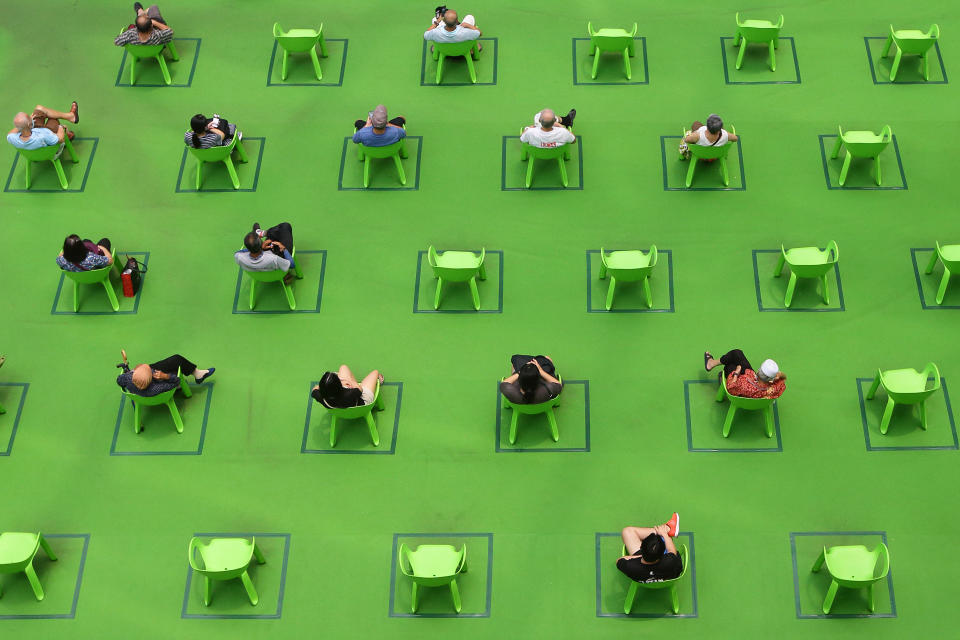 People sit on a chair marked out to keep social distancing amid the COVID-19 pandemic on March 19, 2021 in Singapore. (Photo by Suhaimi Abdullah/NurPhoto via Getty Images)