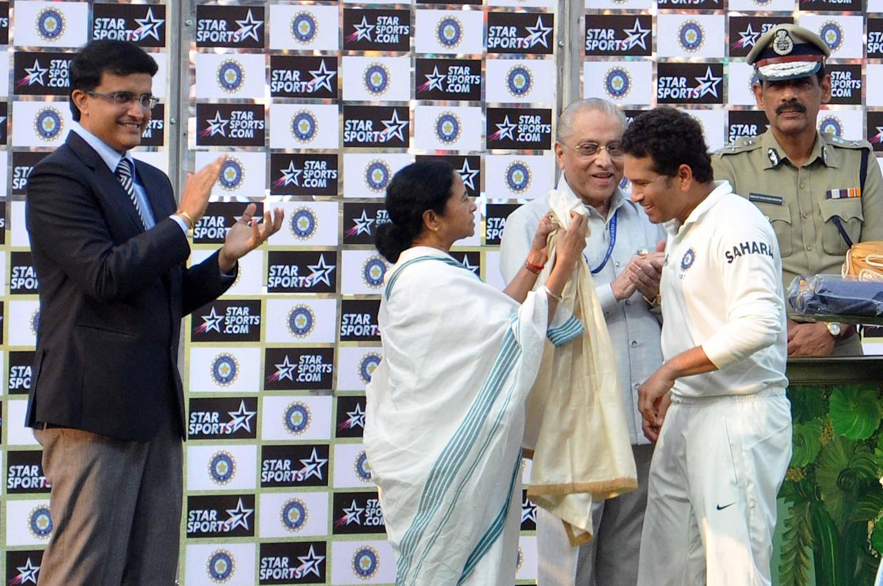 West Bengal Chief Minister Mamata Banerjee, former BCCI President Jagmohan Dalmiya and Kolkata Police Commissioner Surajit Kar Purkayastha clap as former cricketer Sourav Ganguly hugs master blaster Sachin Tendulkar as India won 1st test match between India and West Indies at Eden Gardens, Kolkata on Nov. 8, 2013. (Photo: IANS)