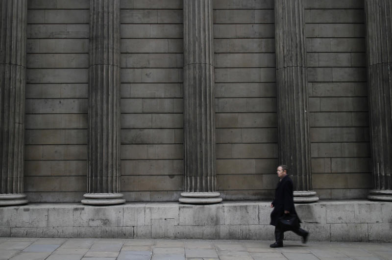 A pedestrian walks past the outside pillars of the Bank of England in the City of London, Monday, Feb. 25, 2013.  The British pound is recovering after dropping against the world's leading currencies as markets reacted to a downgrade of the U.K.'s cherished triple-A credit rating.  The pound was in focus in the wake of last Friday's decision by Moody's to downgrade the U.K.'s credit rating by one notch from the top AAA to AA1. The agency says sluggish growth and rising debt are weakening the British economy's outlook. (AP Photo/Alastair Grant)