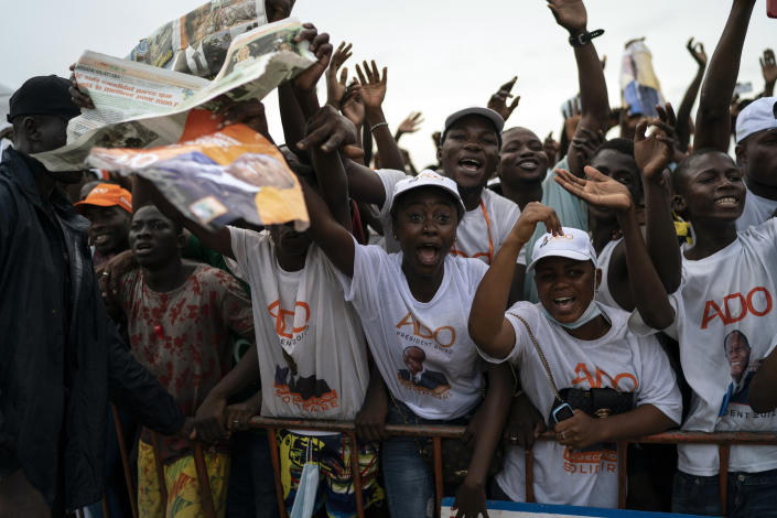 Supporters cheer as Ivory Coast President Alassane Ouattara arrives at a rally in Anyama, in the outskirts of Abidjan, Ivory Coast, Wednesday, Oct. 28, 2020. Ouattara, who first came to power after the 2010 disputed election whose aftermath left more than 3,000 people dead, is now seeking a third term in office. The candidate maintains that he can serve a third term because of changes to the country's constitution, though his opponents consider his candidacy illegal. (AP Photo/Leo Correa)