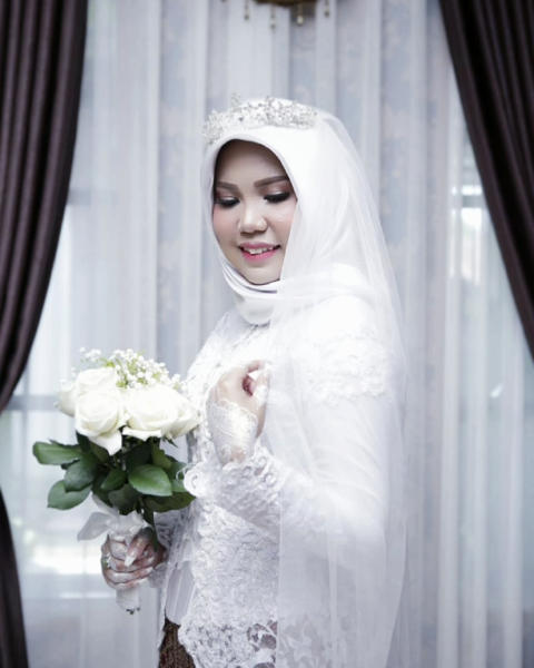 In this photo taken on Sunday, Nov. 11, 2018, and released by Intan Syari, Indonesian Intan Syari poses in her wedding dress with a bouquet of flowers on the day of her planned wedding in Pangkal Pinang, Indonesia. Syari who was engaged to a man who died on a Lion Air flight that plunged into the sea has worn her wedding dress on the day they were to have been married. Intan Syari's fiance, medical doctor Rio Nanda Pratama, was among 189 people on the Boeing 737 MAX 8 plane who died when it crashed a few minutes after taking off from Jakarta on Oct. 29. (AP Photo)