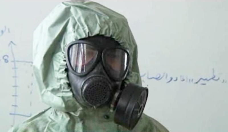 This image made from an AP video posted on Wednesday, Sept. 18, 2013 shows a student wearing a gas mask and protective suit during a classroom session a on how to respond to a chemical weapons attack in Aleppo, Syria. In a disused classroom of a school in the northern Syrian city of Aleppo, a group of volunteers learned how to deal with a chemical weapons attack. The drills came amid continued diplomatic wrangling over how to collect Syria's arsenal of chemical and biological agents to prevent any repeat of the August 21 attack outside Damascus that, according to the US, was carried out by Syrian regime and killed more than 1,400 people, including at least 400 children. (AP Photo via AP video)