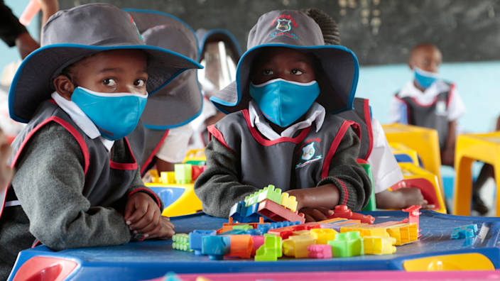 Students wearing face masks and hats in a class sitting at a table covered in Lego on the first day of re-opening schools in Ruwa, Zimbabwe - Monday 22 March 2021