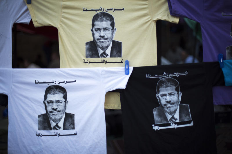"""T-shirts with the face of Egypt's ousted President Mohammed Morsi are displayed for sale at Nasr City, where protesters have installed a camp and hold daily rallies, in Cairo, Egypt, Monday, July 29, 2013. Europe's top diplomat urged Egypt's government to reach out to the Muslim Brotherhood as she worked Monday to mediate an end to the country's increasingly bloody crisis, while the mainly Islamist protesters calling for the return of ousted leader Mohammed Morsi massed for more protests. Arabic on the shirts reads, """"Morsi is our president,"""" and """"yes to legitimacy."""" (AP Photo/Manu Brabo)"""