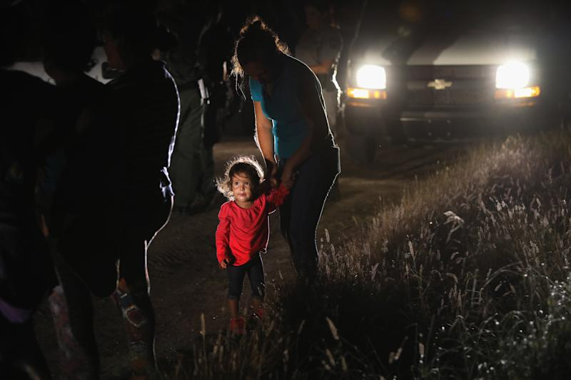 A 2-year-old Honduran stands with her mother after being detained by U.S. Border Patrol agents near the U.S.-Mexico border on June 12. (John Moore via Getty Images)