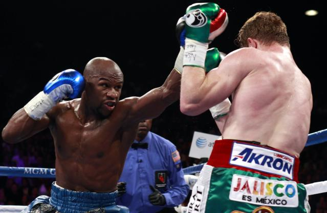 Floyd Mayweather Jr. (L) of the U.S. throws a punch at WBC/WBA 154-pound champion Canelo Alvarez during their title fight at the MGM Grand Garden Arena in Las Vegas, Nevada, September 14, 2013. REUTERS/Steve Marcus (UNITED STATES - Tags: SPORT BOXING)