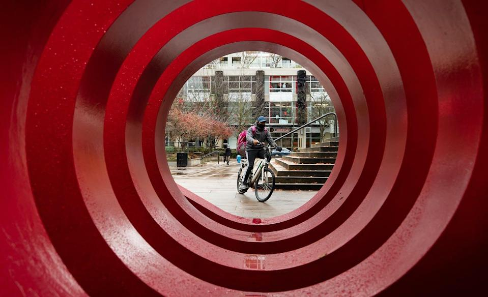 """<span class=""""caption"""">A food delivery worker wearing a face mask to help curb the spread of COVID-19 is framed by a large public art installation while riding a bike in Vancouver in November 2020. </span> <span class=""""attribution""""><span class=""""source"""">THE CANADIAN PRESS/Darryl Dyck</span></span>"""