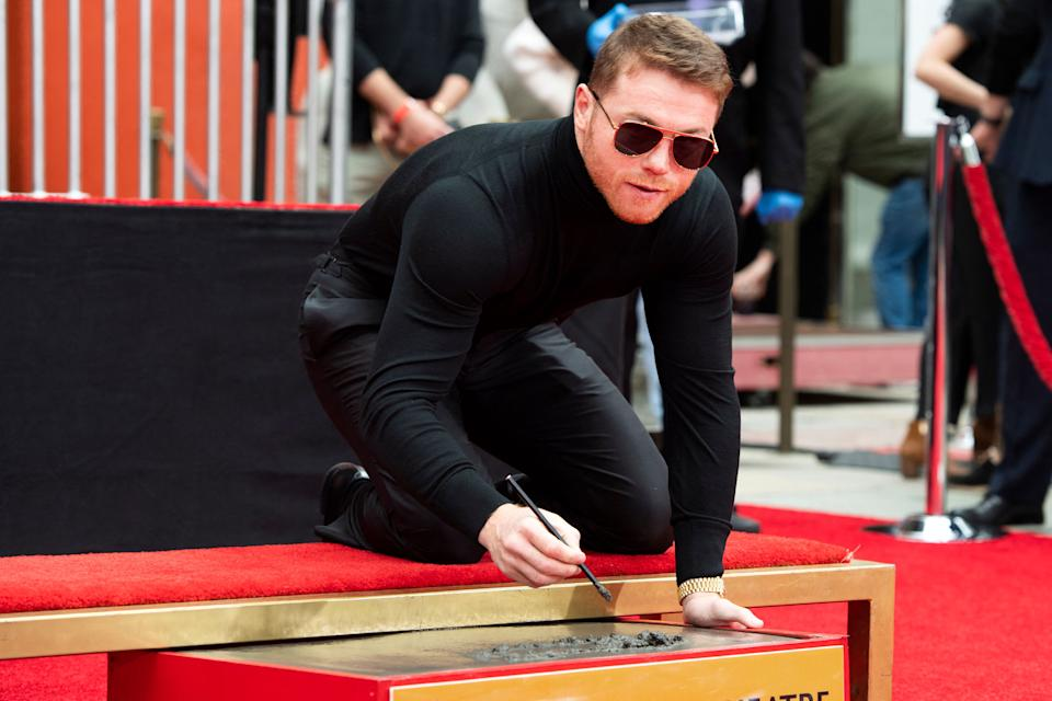 Boxer Canelo Alvarez signs the ciment at his Hand and Footprint Ceremony at TCL Chinese Theatre, in Hollywood, California, March 20, 2021. (Photo by VALERIE MACON / AFP) (Photo by VALERIE MACON/AFP via Getty Images)