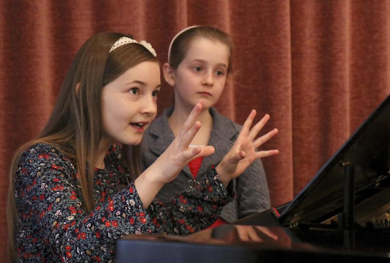 In this Nov. 17, 2016 picture Alma Deutscher and her sister Helen Deutscher, from left, play piano during a rehearsal in Vienna, Austria. Alma Deutscher is a composer, virtuoso pianist and concert violinist who wrote her first sonata five years ago and whose first full opera will have its world premiere next month. All of which is special only because she 11. (AP Photo/Ronald Zak)