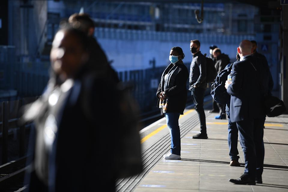 Commuters stand apart as they wait for a train at Canning Town underground station in London, after the announcement of plans to bring the country out of lockdown.