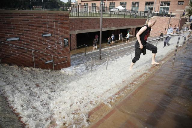 A man walks through flood water up stairs from a parking structure outside UCLA's Pauley Pavilion sporting arena as water flows from a broken thirty inch water main that was gushing water onto Sunset Boulevard near the UCLA campus in the Westwood section of Los Angeles July 29, 2014. The geyser from the 100-year old water main flooded parts of the campus and stranded motorists on surrounding streets. REUTERS/Danny Moloshok (UNITED STATES - Tags: DISASTER ENVIRONMENT)