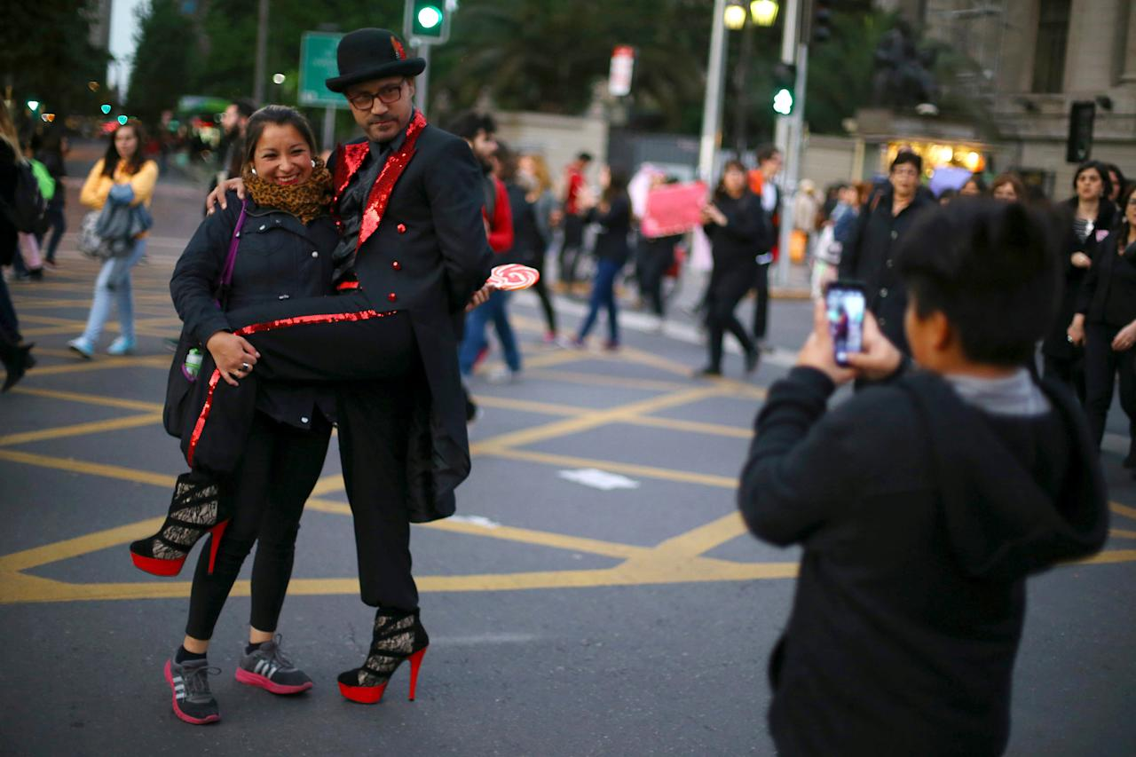 A demonstrator wearing high heels poses during a peaceful march against gender violence in Santiago, Chile, October 19, 2016. REUTERS/Ivan Alvarado