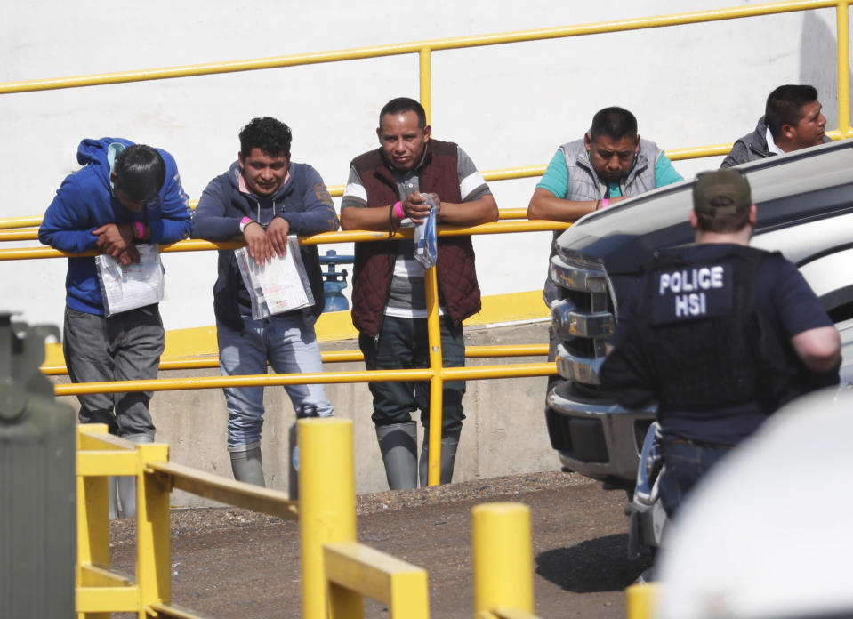 FILE - In this this Aug. 7, 2019, file photo, handcuffed workers await transportation to a processing center following a raid by U.S. immigration officials at Koch Foods Inc., plant in Morton, Miss. Federal officials announced Thursday, Aug. 6, 2020, the indictments of four executives from two Mississippi poultry processing plants on federal charges tied to one of the largest workplace immigration raids in the U.S. in the past decade. (AP Photo/Rogelio V. Solis, File)