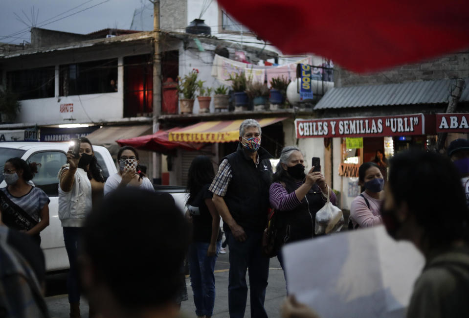 Residents watch a march demanding justice for the people who died in Monday's subway collapse, in Mexico City's south side, Friday, May 7, 2021. An elevated section of Line 12 collapsed late Monday killing at least 25 people and injuring more than 70, city officials said. (AP Photo/Eduardo Verdugo)
