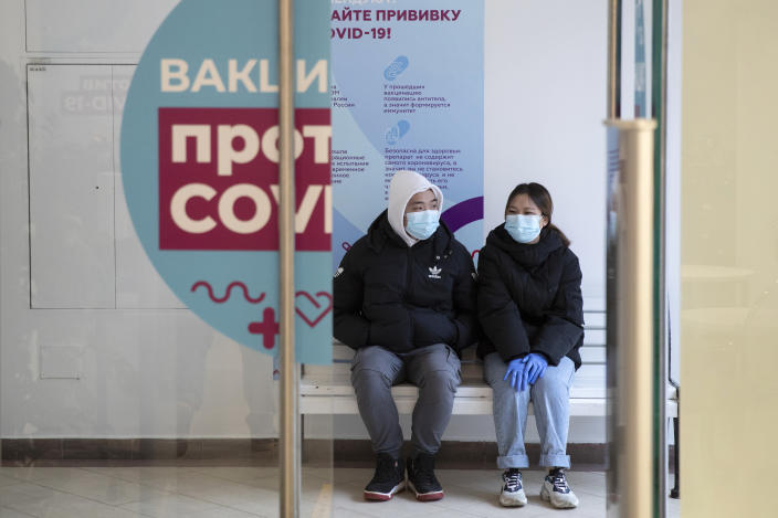A couple wait in a queue to get a shot of Russia's Sputnik V coronavirus vaccine at a vaccination center in GUM State Department store in Moscow, Russia, Wednesday, Jan. 20, 2021. Russia started a mass coronavirus vaccination campaign on Monday. (AP Photo/Pavel Golovkin)