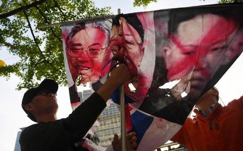 <span>A conservative activist prepares to display partially burnt images of late North Korean leaders Kim Il Sung (L), Kim Jong Il </span> <span>Credit: AFP </span>