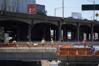 In this Thursday, April 29, 2021, photograph, workers toil on a bridge over the surface of what will become Interstate 70 north of downtown Denver. The elevated roadway that has served as Interstate 70 will be demolished as part of the 10-mile-long project, which will cost $1.2 billion by completion by winter 2022. (AP Photo/David Zalubowski)